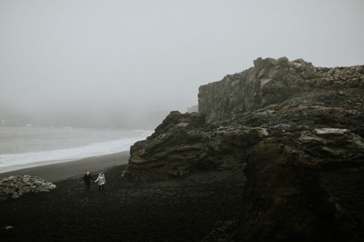 couple walking in the rain on Black sand beach