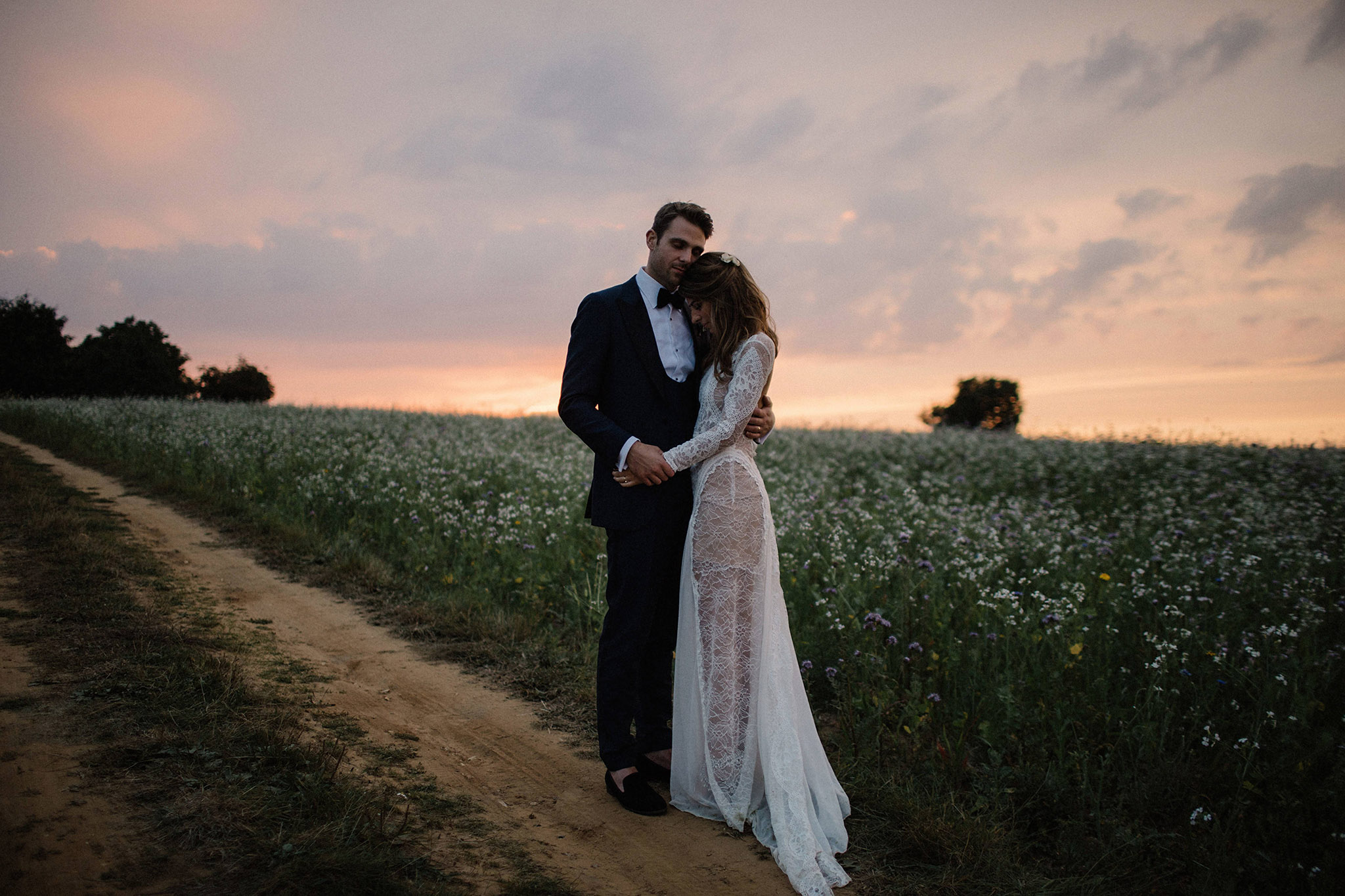 bride and groom hugging in the sunset