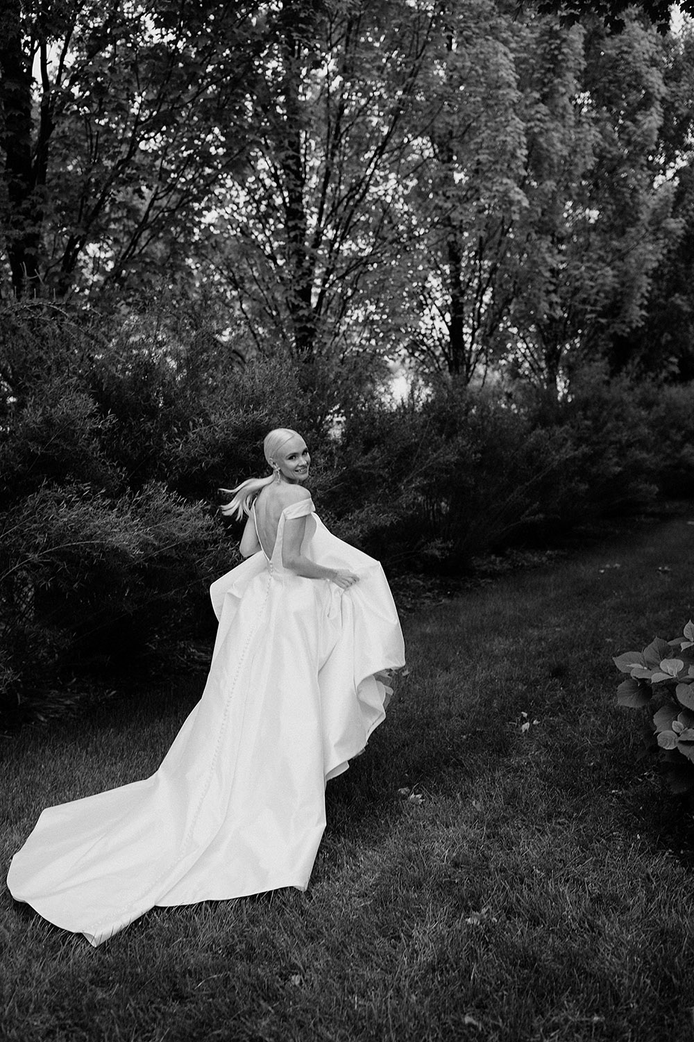 Bride running through gardens with modern wedding dress